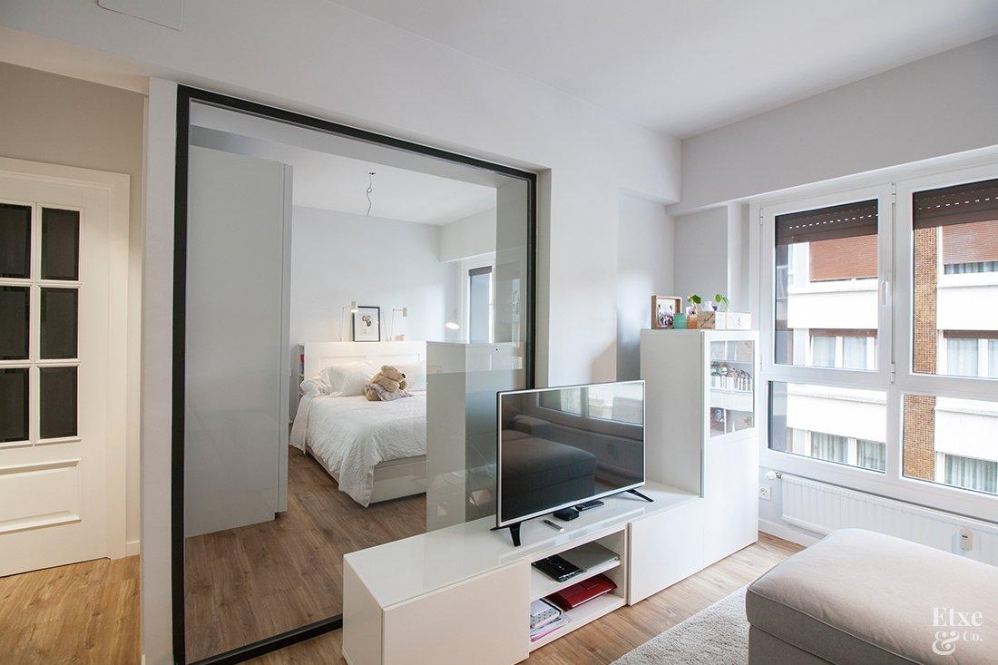 Reforma de Etxe And Co en la que se ha colocado un panel de cristal entre el dormitorio y el salón para conseguir más luz en la vivienda.