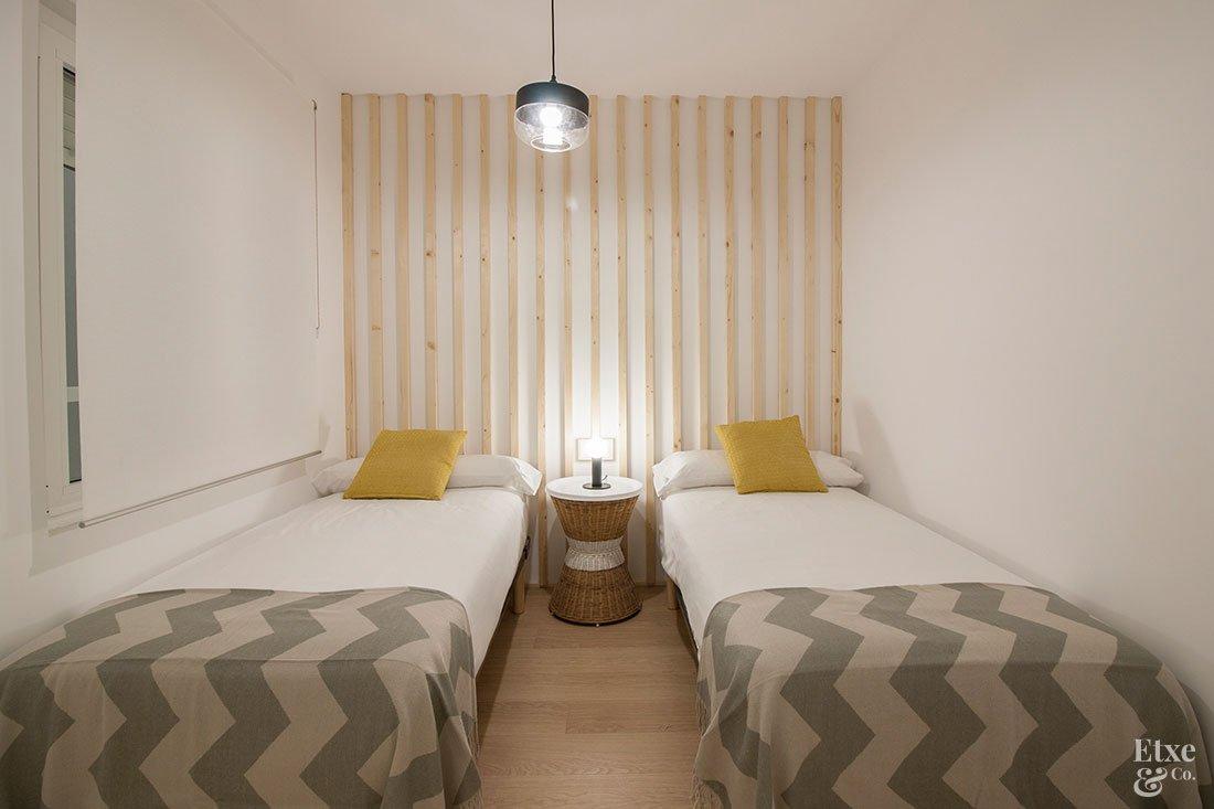 Uno de los tres dormitorios reformados con cabecero de listones de madera de la vivienda de la calle San Martin